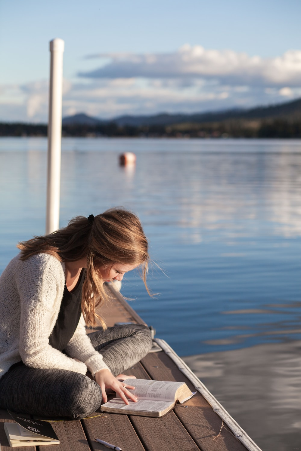 photo of woman reading book near body of water