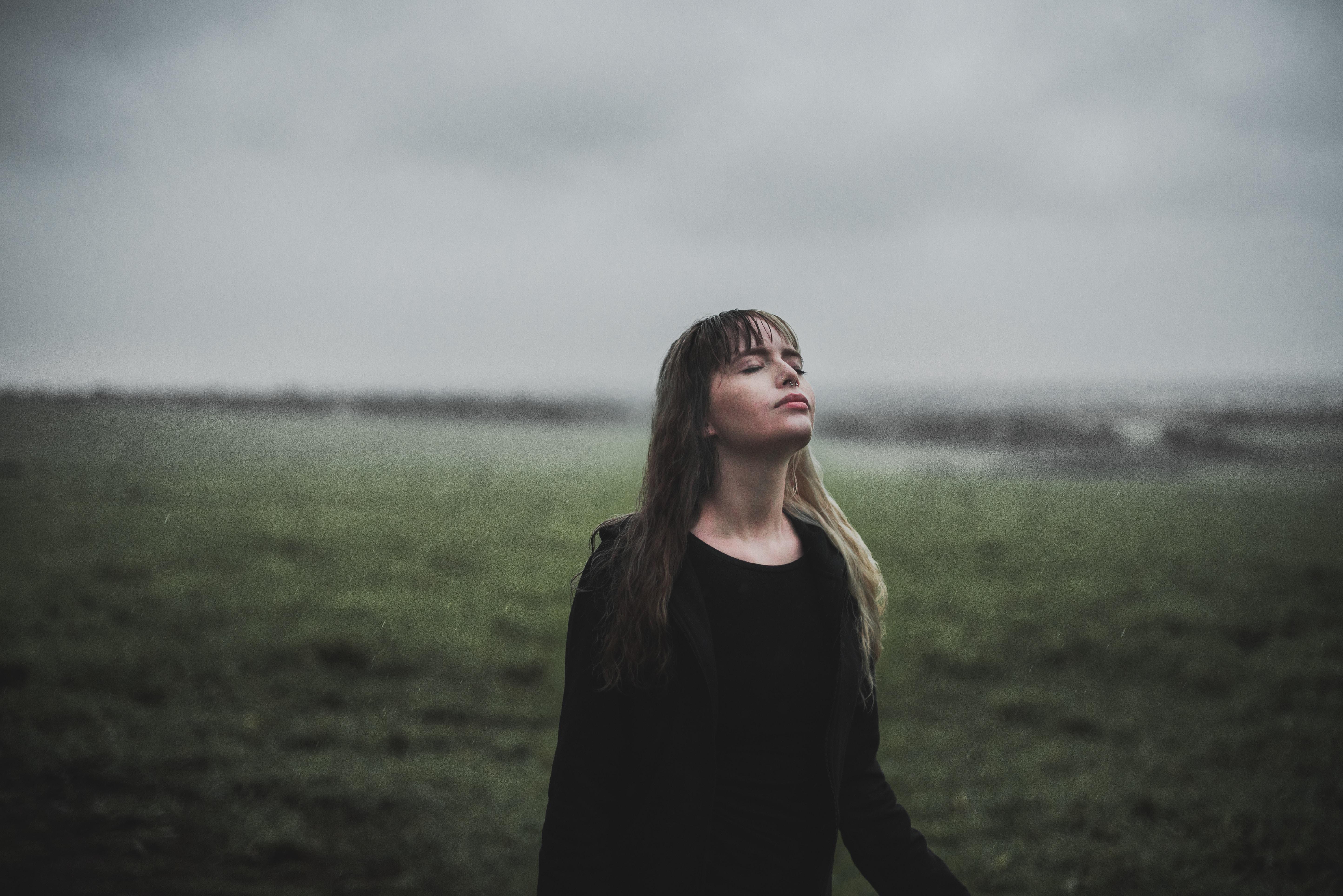 woman facing upward standing on green grass