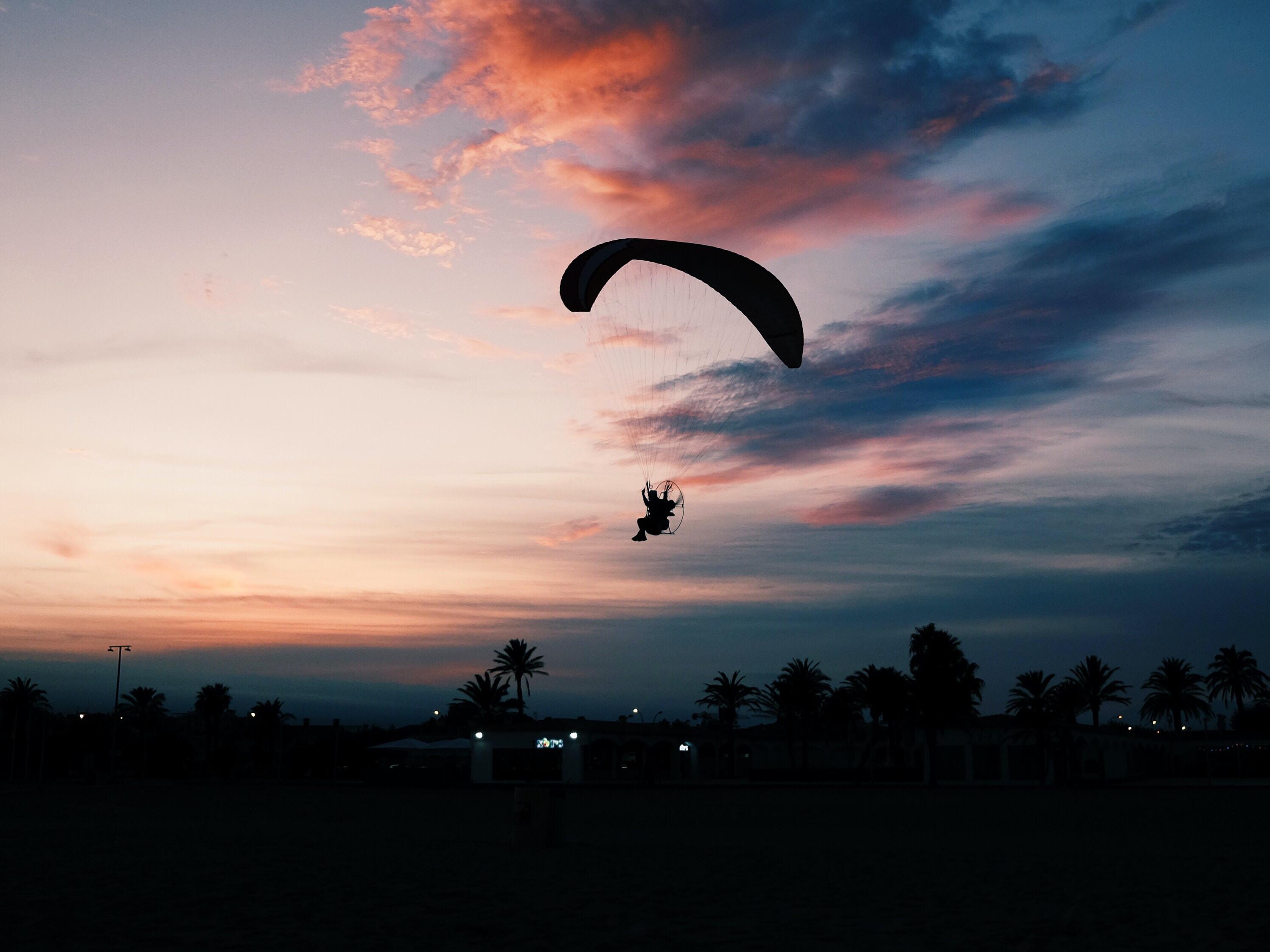 silhouette of man parachuting under gray sky