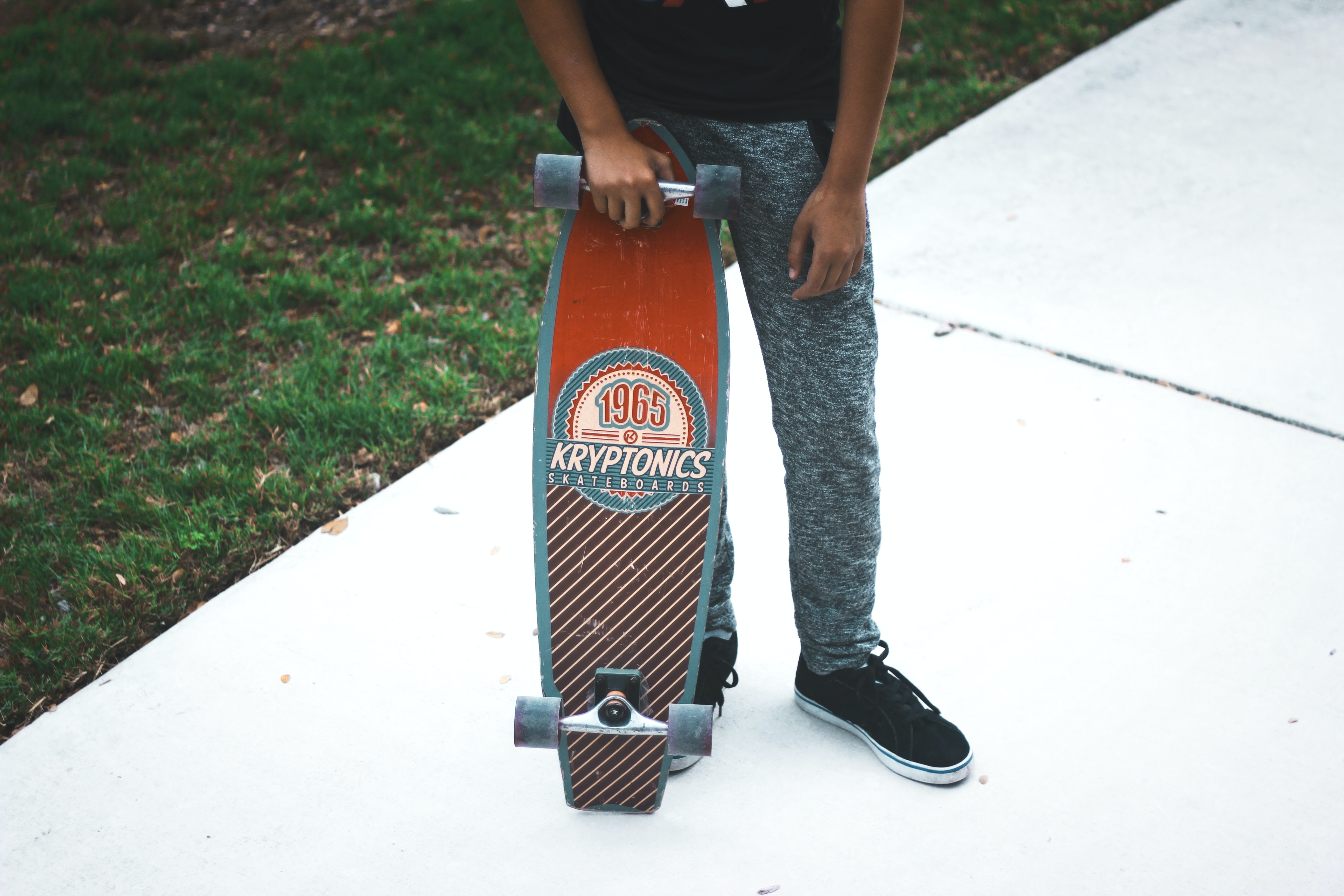 person holding red and gray Kryptonics cruiserboard standing on white tiles