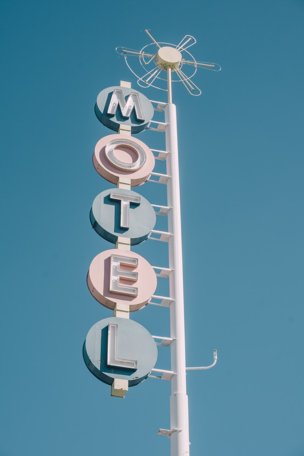 white and teal metal motel signage