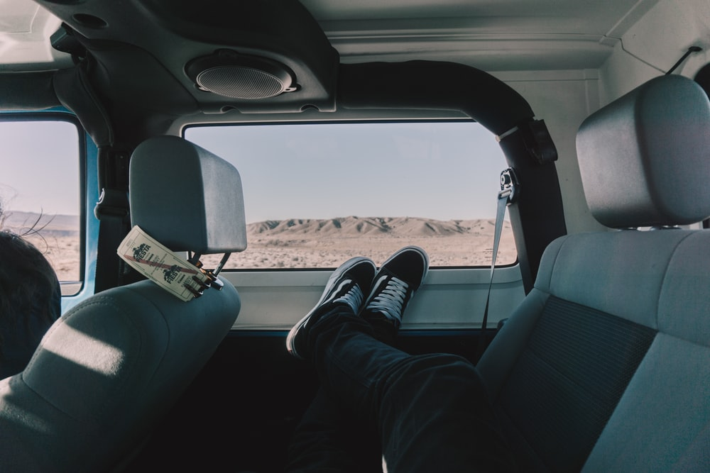 person's both feet on vehicle window