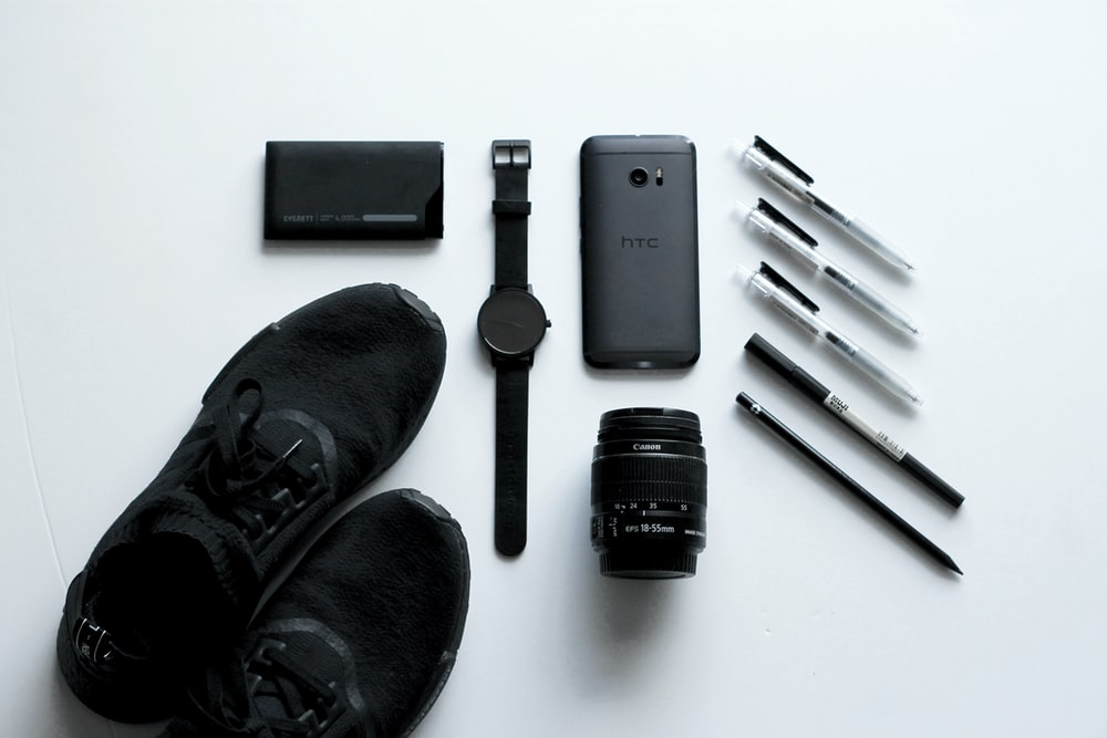 black HTC Android smartphone beside camera lens, ballpoint pens, and lace-up shoes