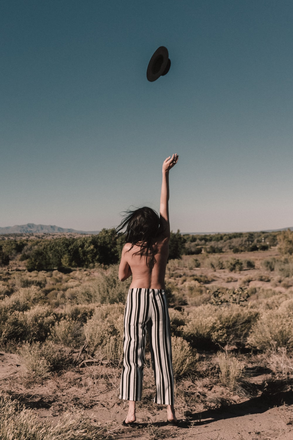 topless person throwing black hat