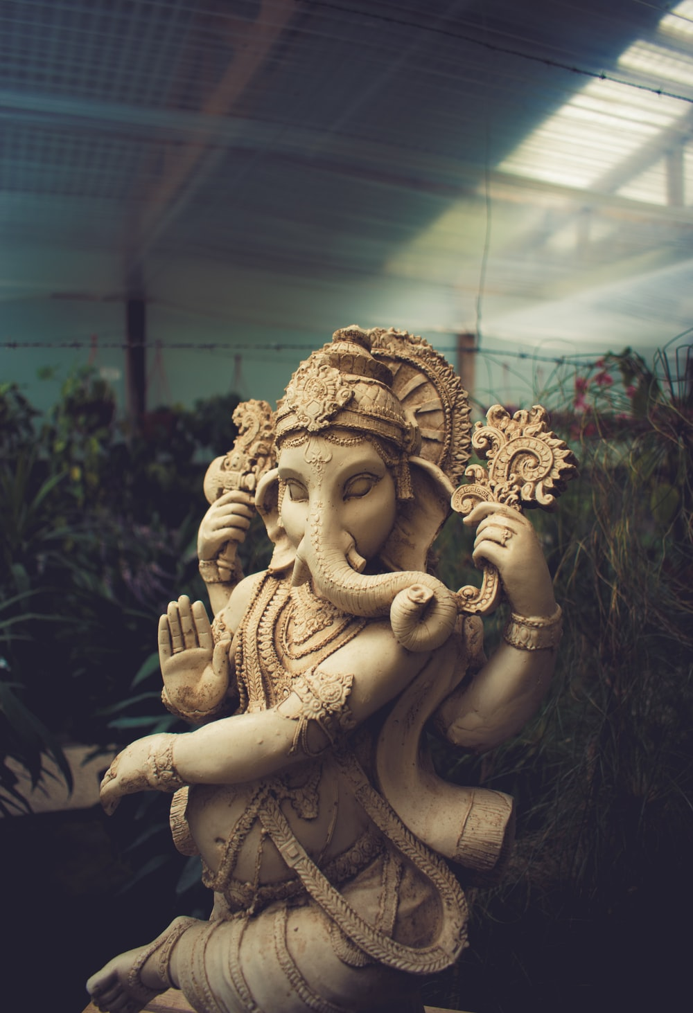 brown concrete Ganesha statue standing behind the plants