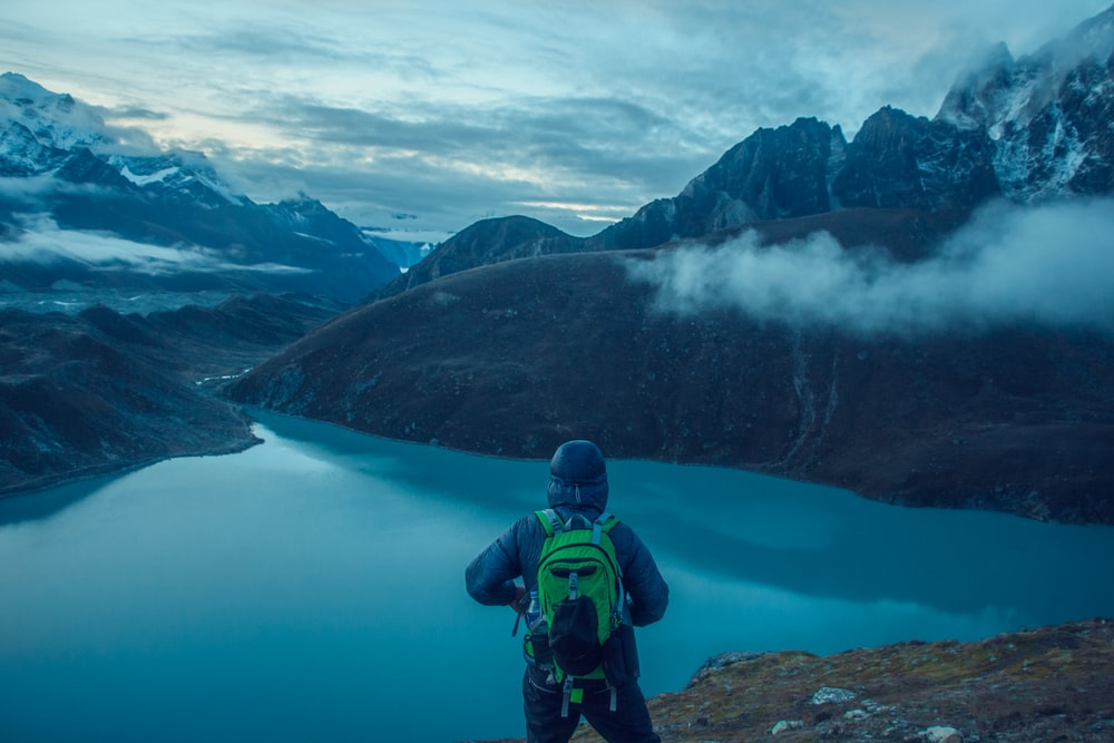person facing lake surrounded with mountains photo