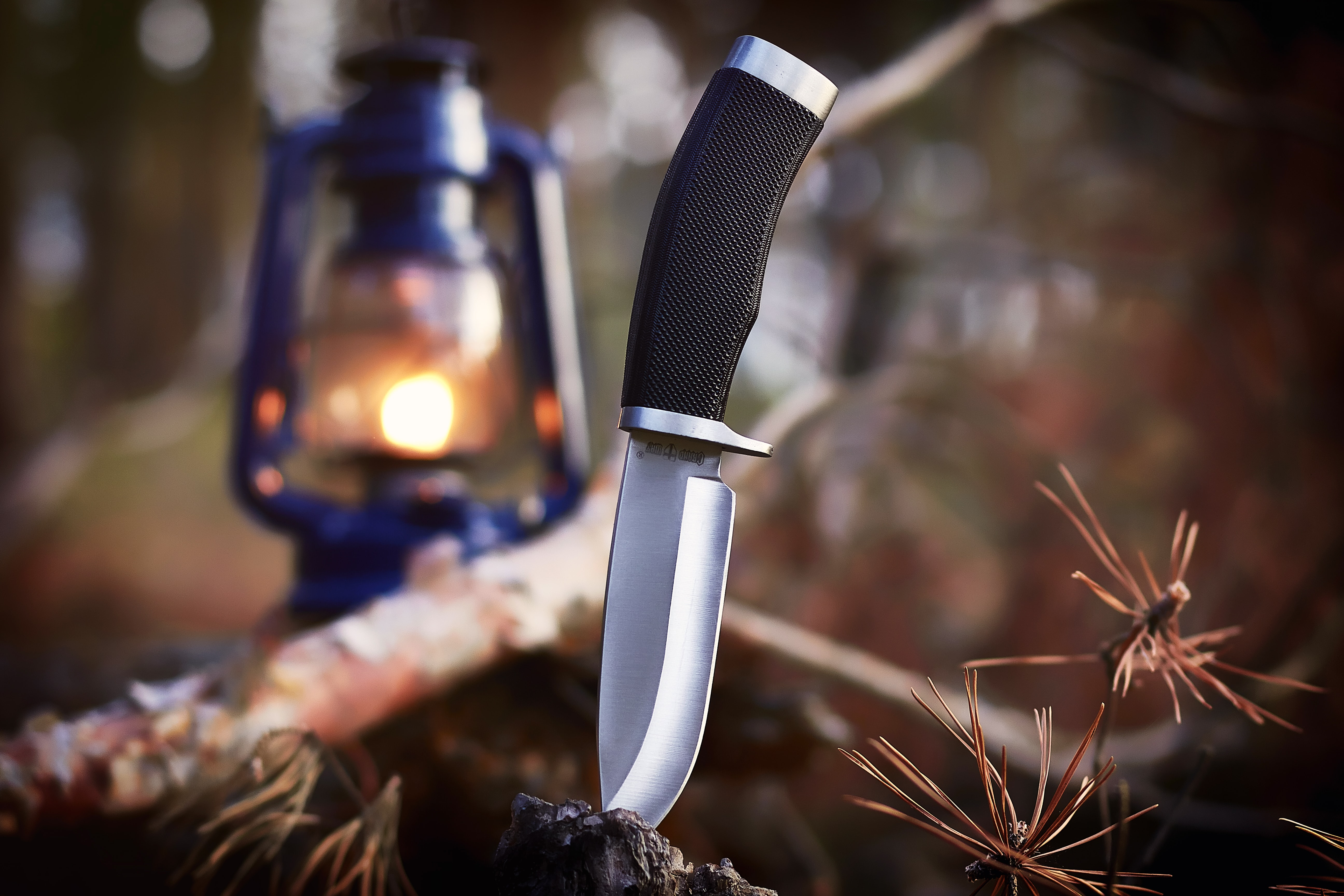black and gray knife dip-in brown wood near blue lantern