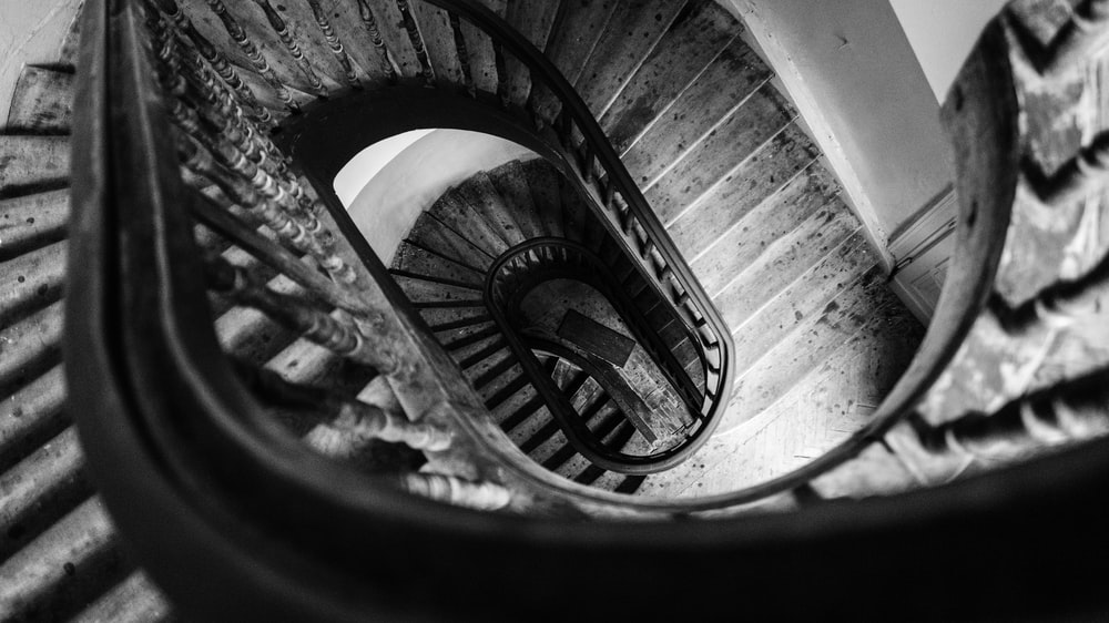 grayscale photo of spiral stair