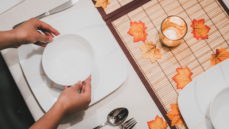 person holding round white ceramic bowl on square white ceramic plate