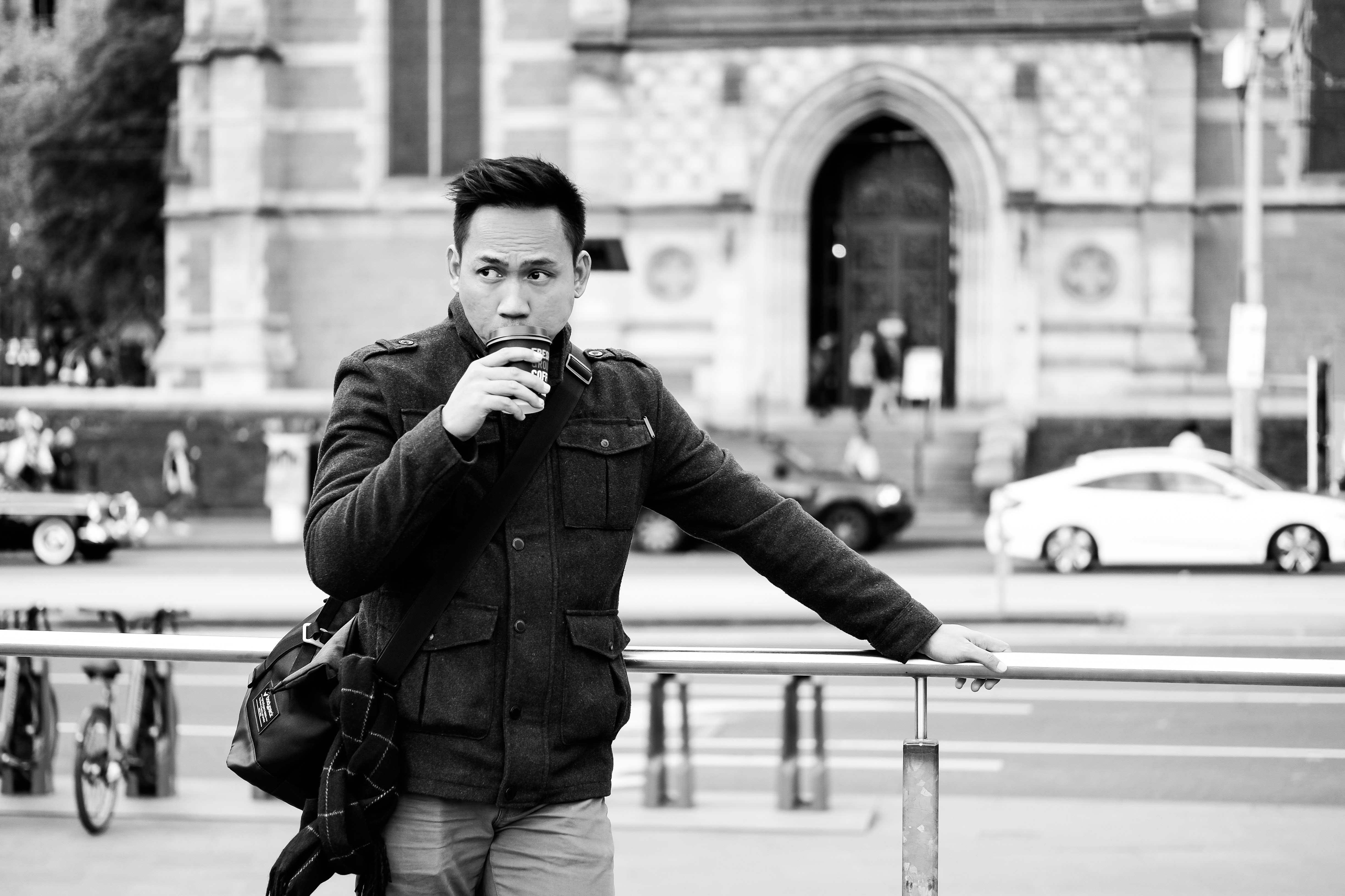 grayscale photo of man drinking on cup while holding on handrail beside road during daytime
