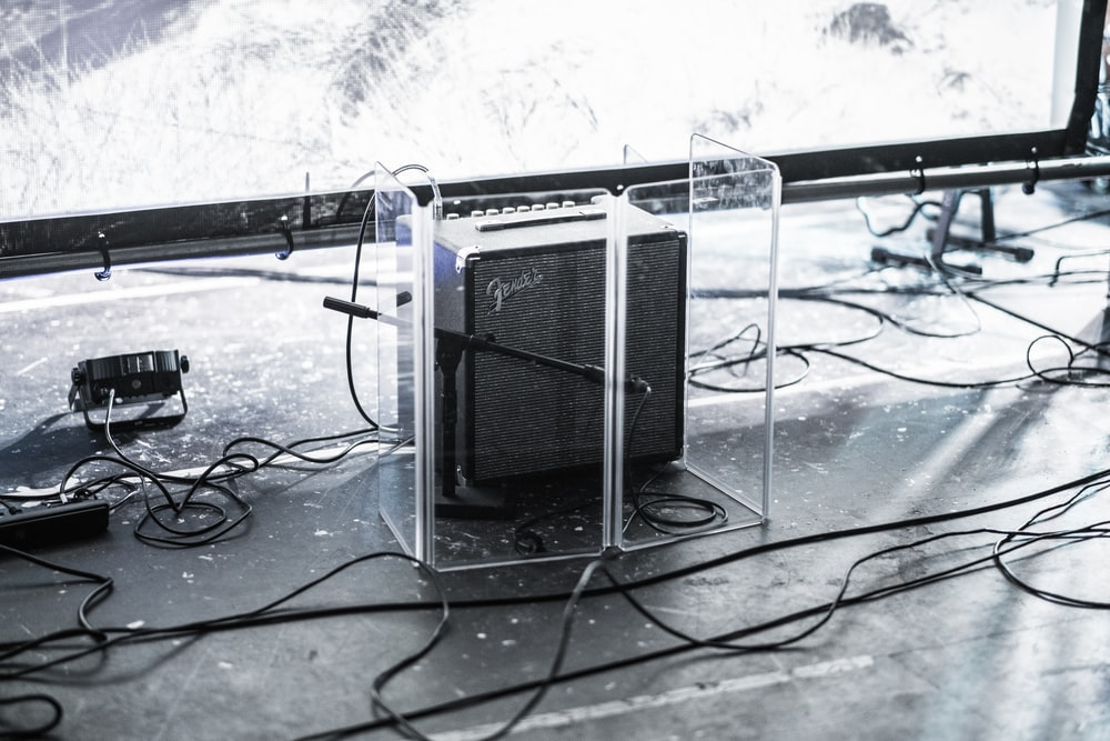 square gray and black Fender guitar amplifier enclosed by clear glass panel on top of stage beside stage lighting
