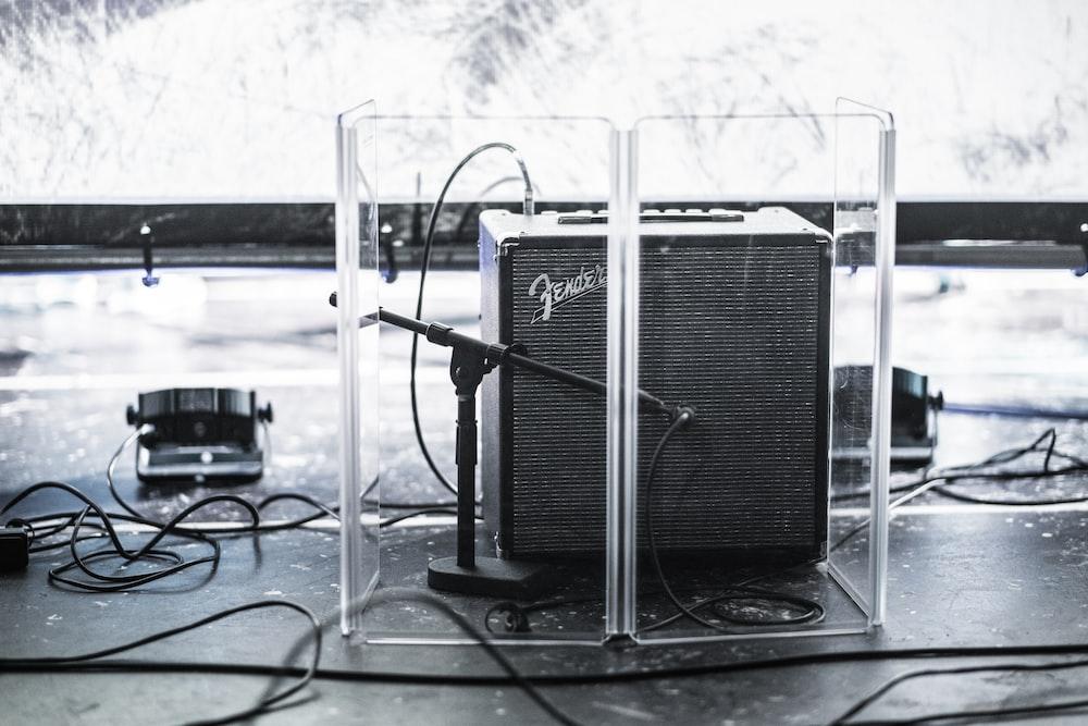 black Fender guitar amplifier in clear acrylic organizer