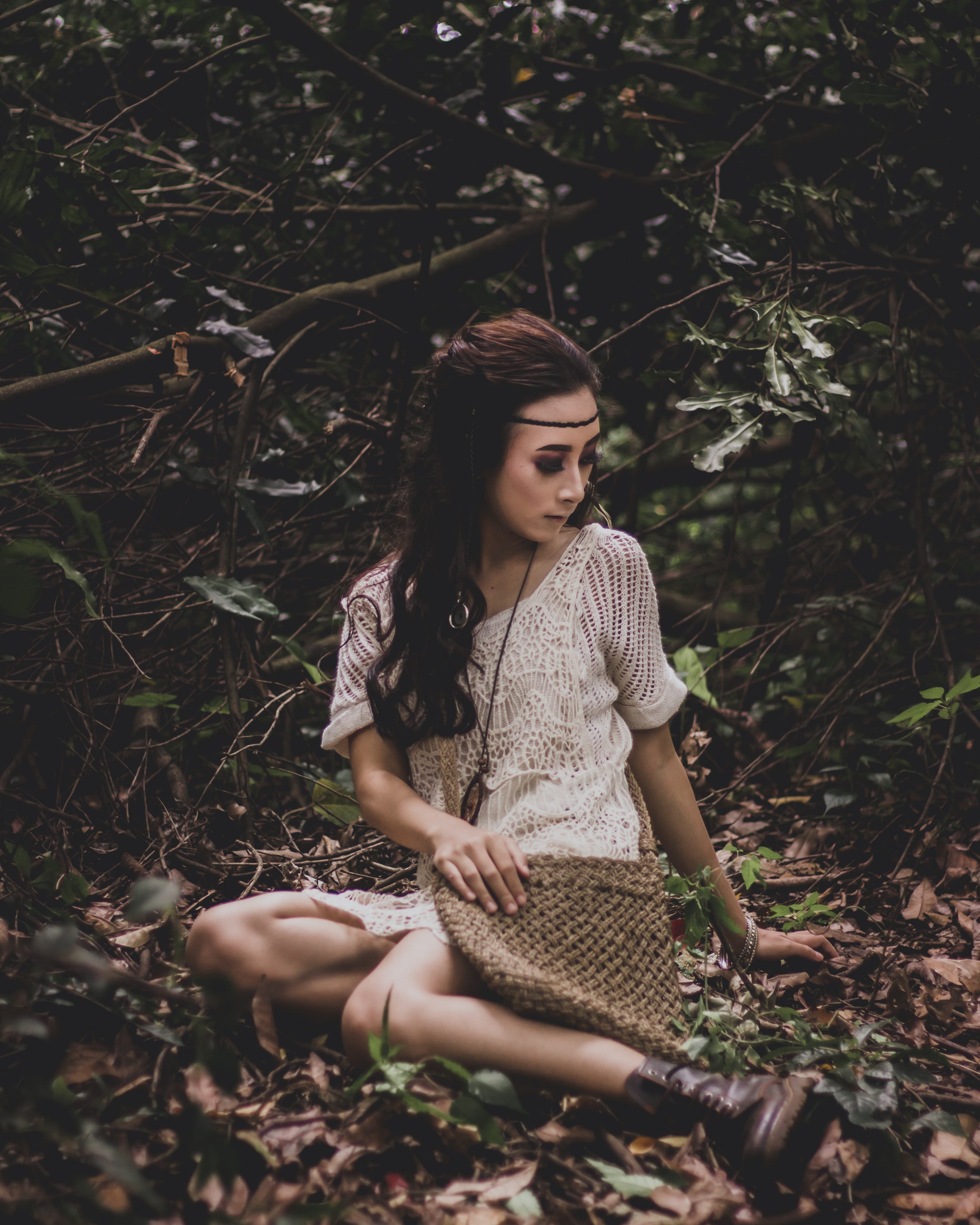 sitting woman on dried leaves surrounded with plants photo