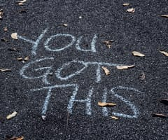 "A photo of the asphalt with ""You Got This"" written in chalk."