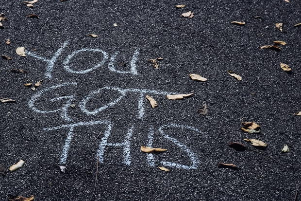 "Picture of the words ""YOU GOT THIS"" scrawled in chalk on asphalt, parly covered by fallen leaves"