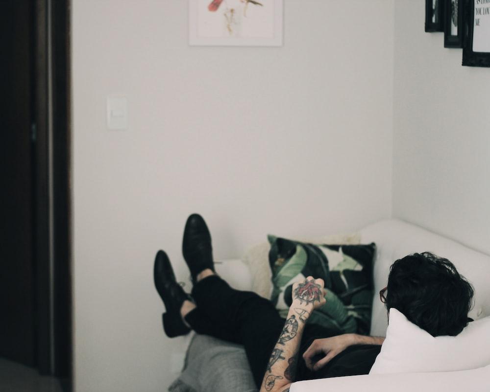man lying on white sofa