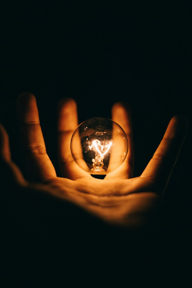 A lit light bulb floating in the air above an open hand