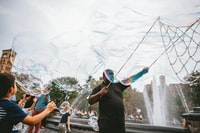 man and boy performing bubble artworks near fountain at daytime