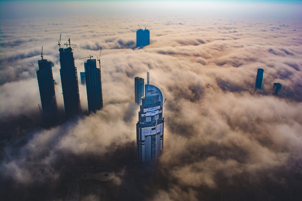 aerial photo of buildings surrounded by clouds during daytime