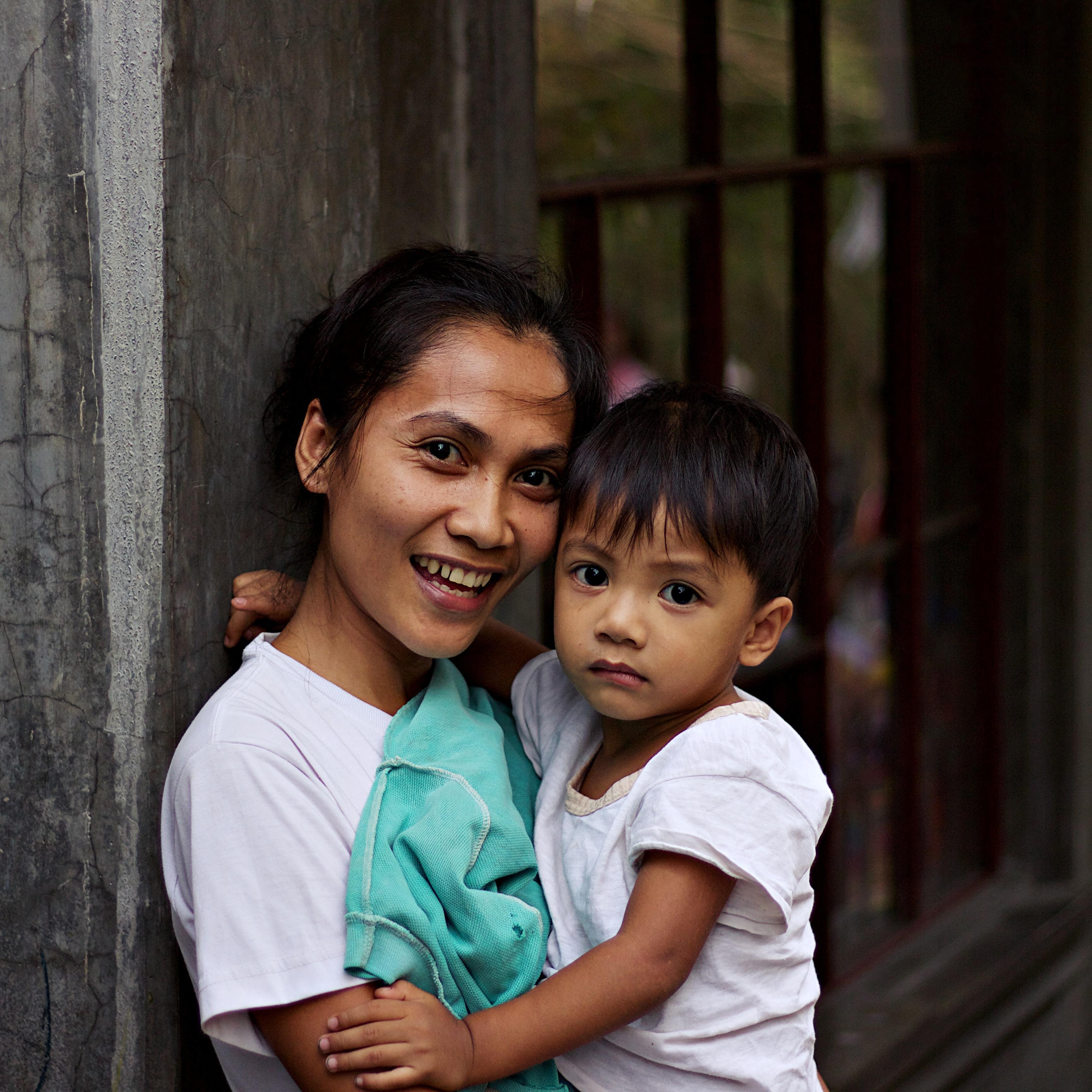 woman carrying a boy near metal frame