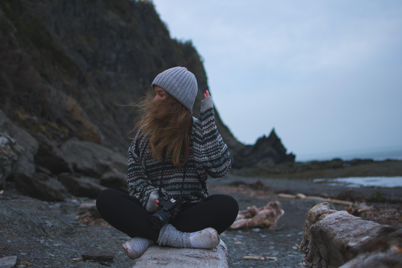 woman wearing gray shirt sitting near seashore