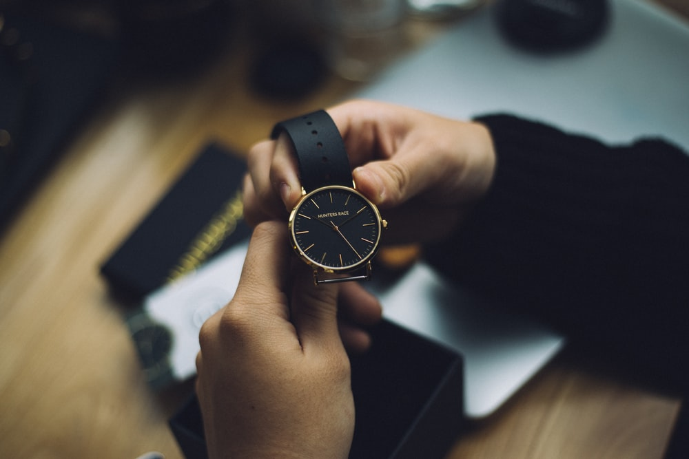 person holding gold-colored analog watch with black strap