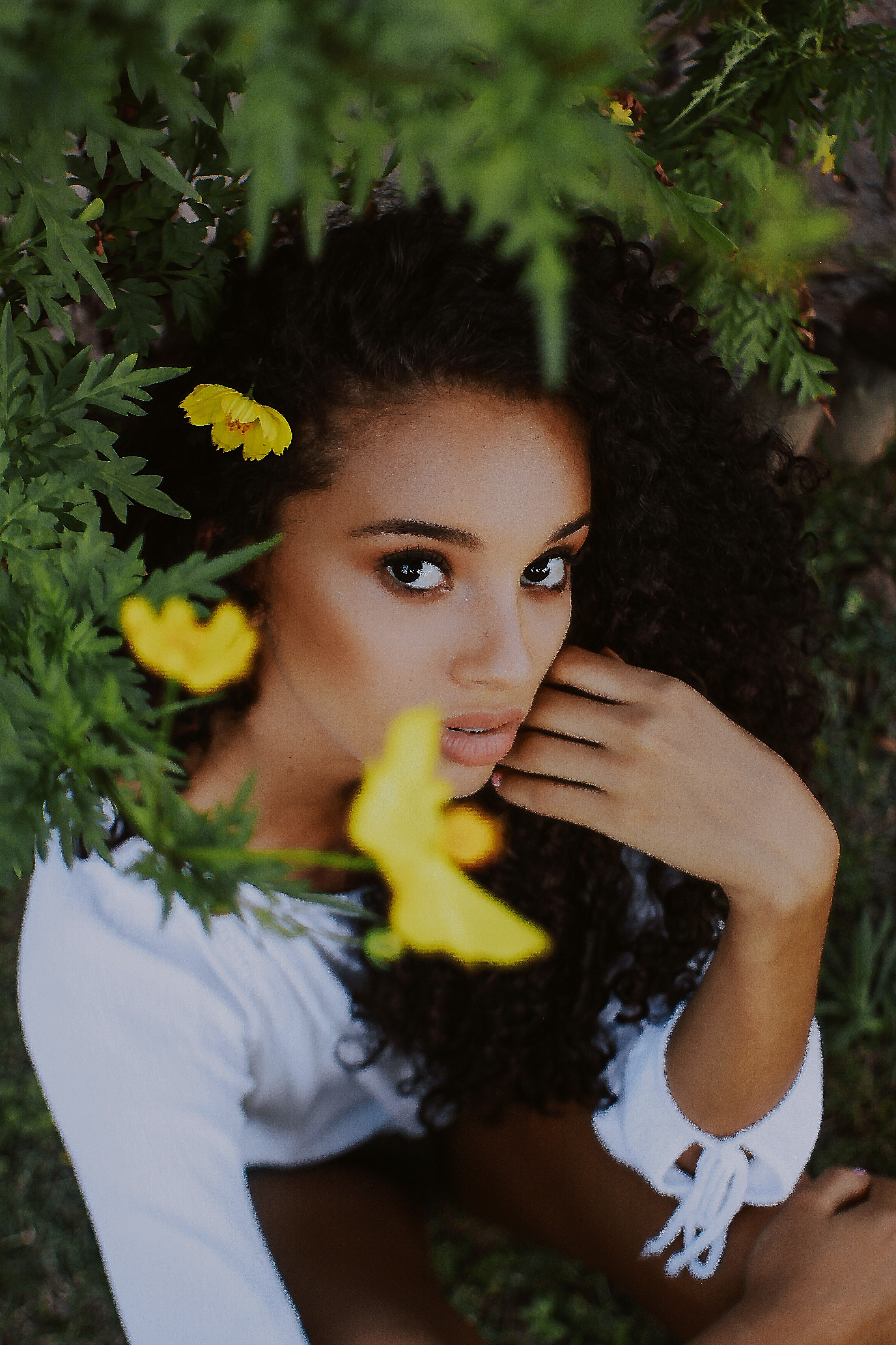 women's white scoop-neck long-sleeved blouse beside yellow petaled flower plants during daytime