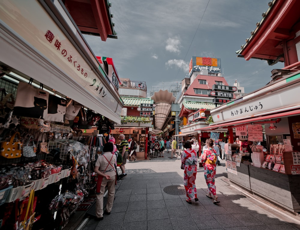 two women walking between buildings
