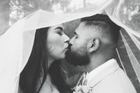 grayscale photo of kissing wedded man and woman under veil