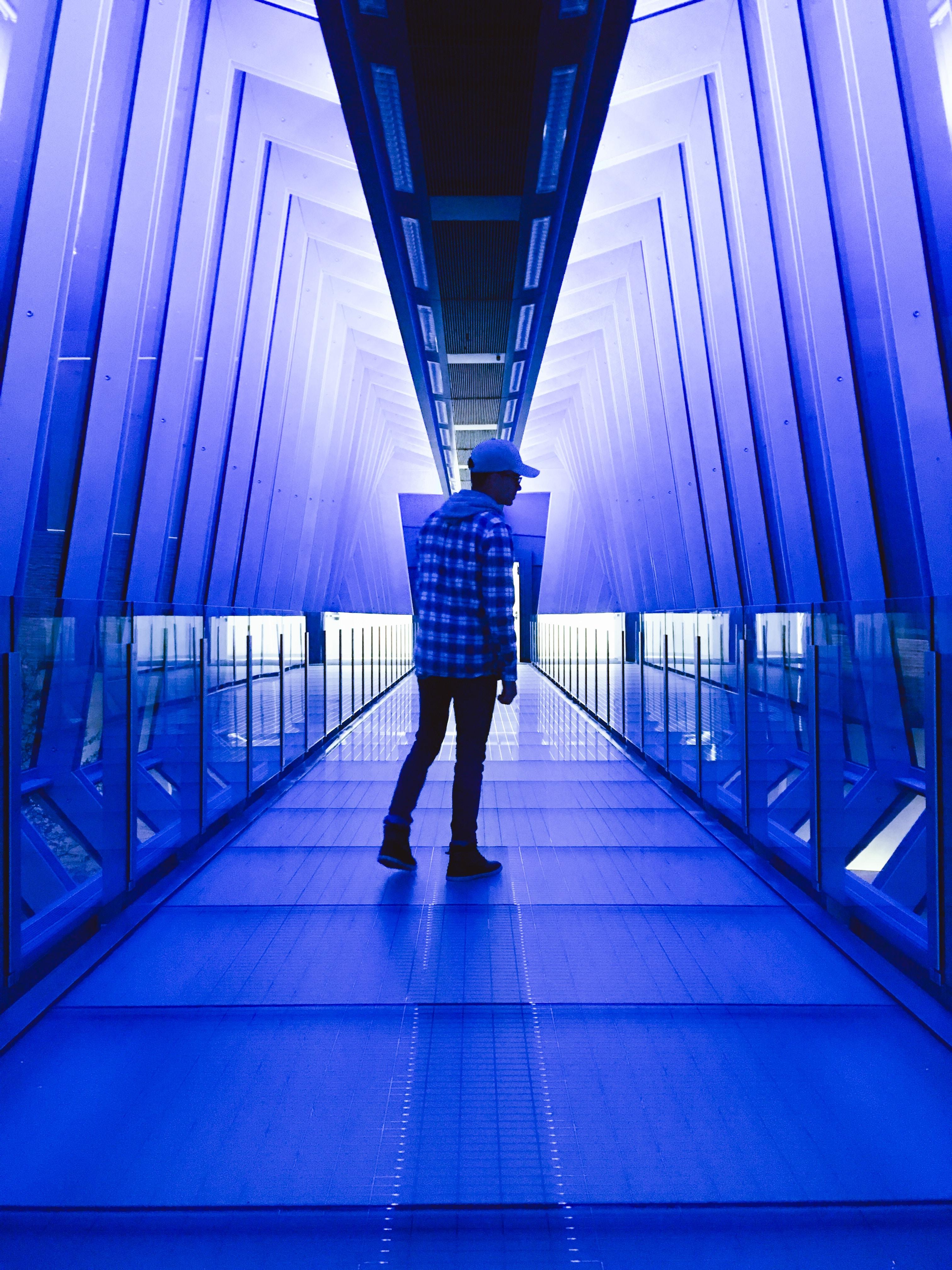 man standing between walls with blue lights