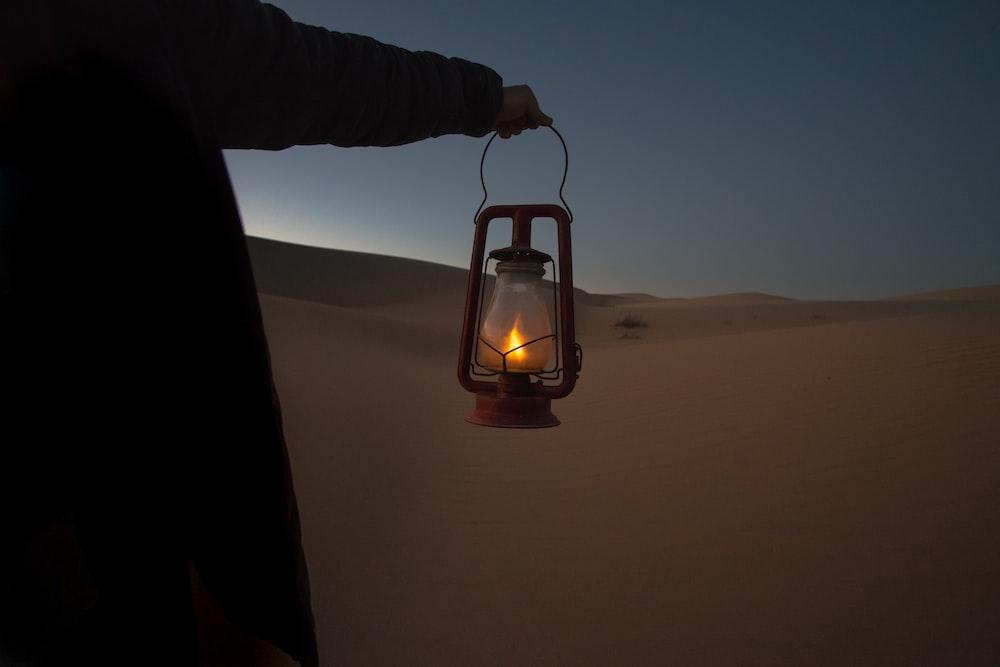 person holding red kerosene lantern