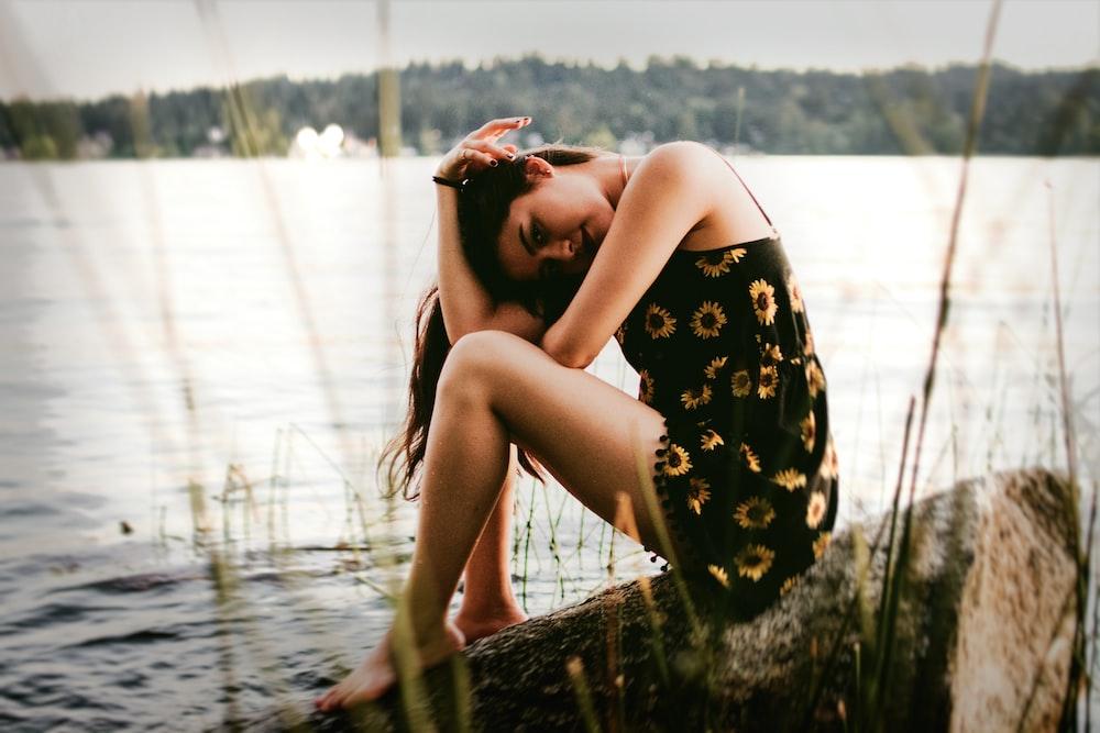 woman sitting on rock near water