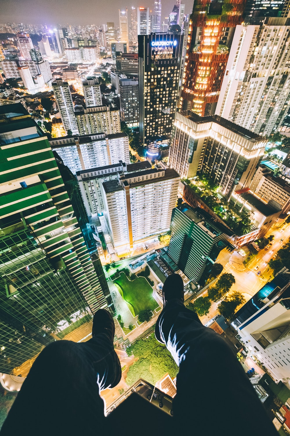 man sitting on top of high-rise buildings
