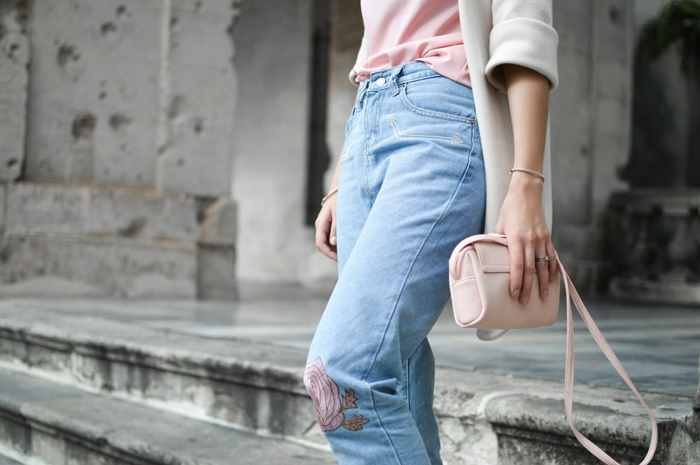 women holding pink leather crossbody bag on stair