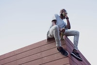 man sit on roof top while holding phone and bottle