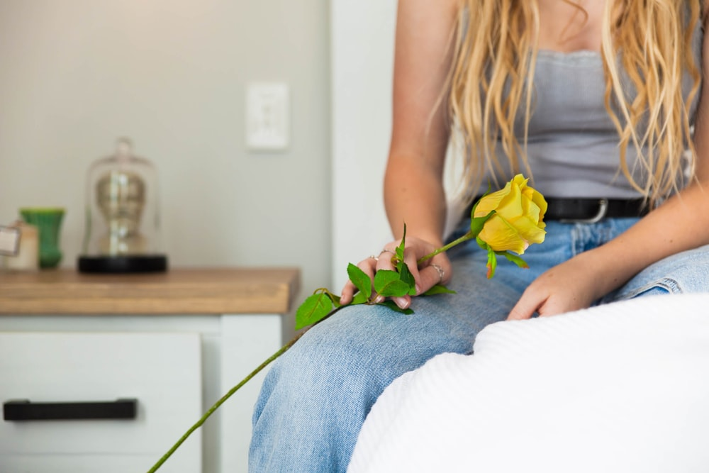 woman holding yellow rose flower sitting on bed