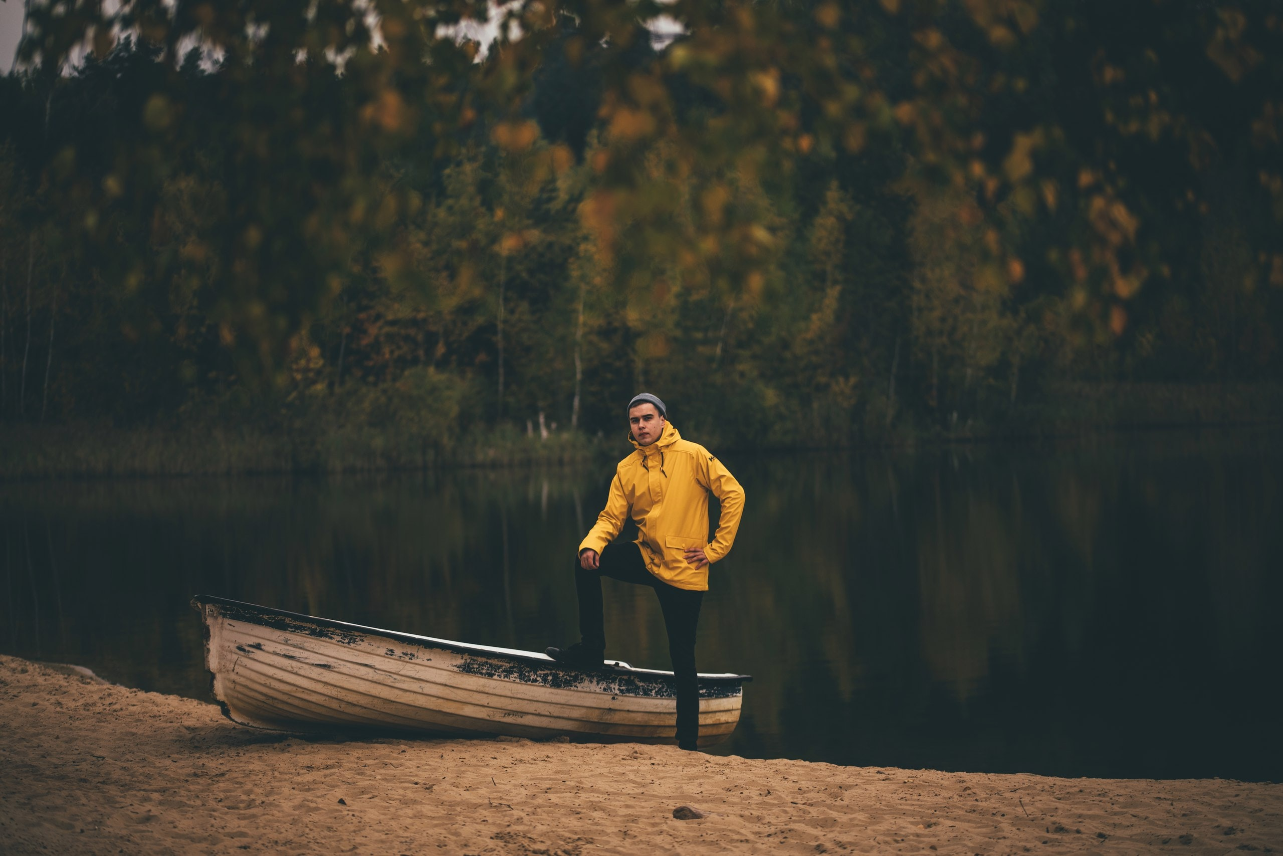 man wearing yellow pullover hoodie standing near white boat during daytime