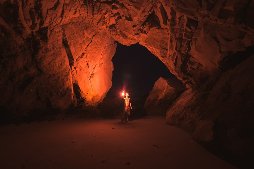 man holding red light flare inside cave