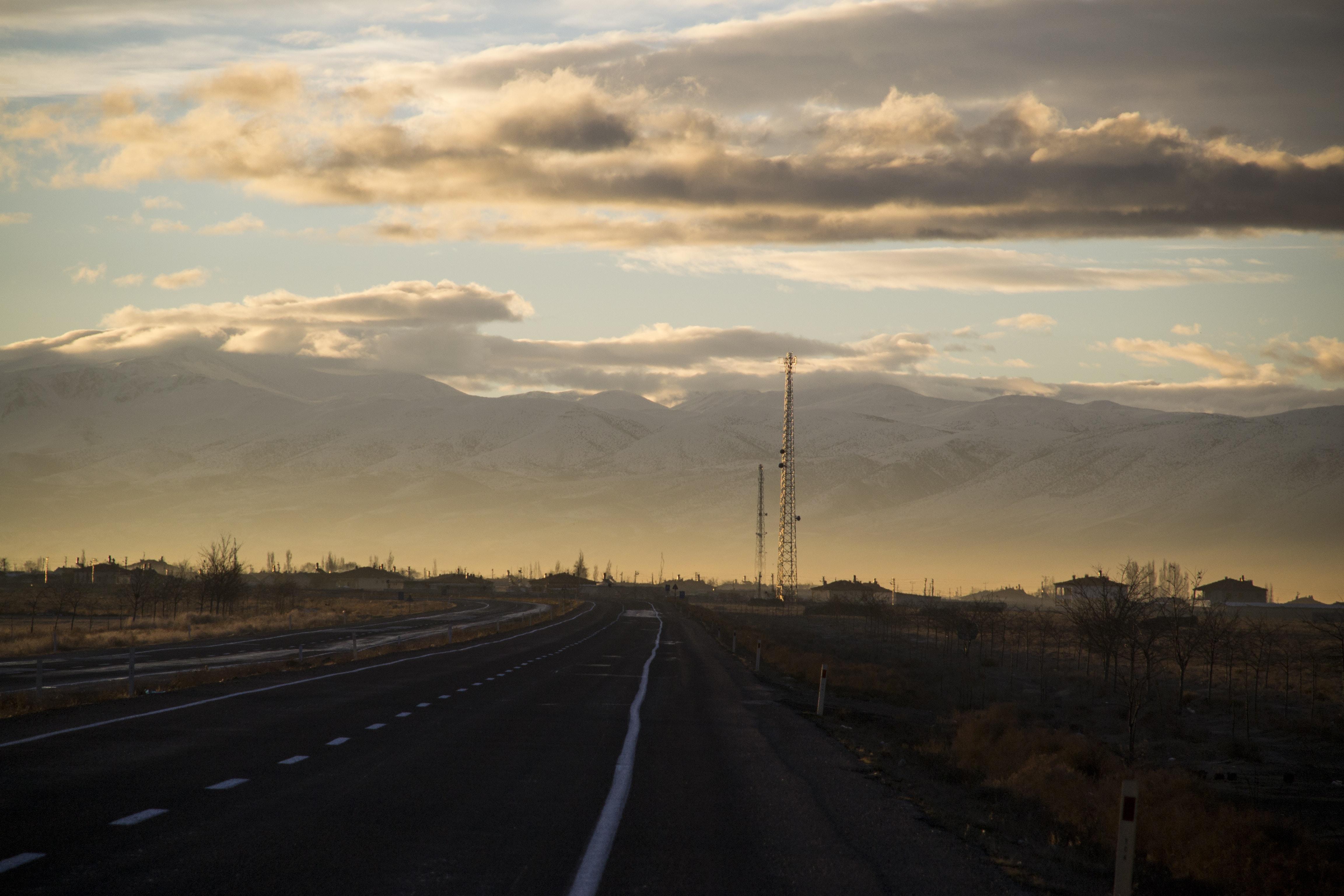 winding road under cumulus clouds
