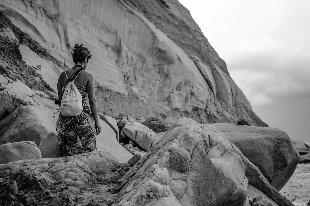 grayscale photography of person walking along outcrop