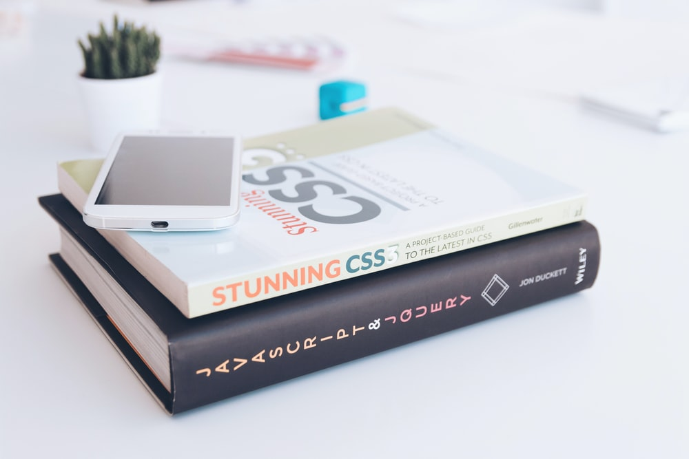 white smartphone on two softbound books