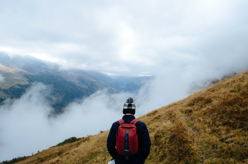 man with red backpack on top of foggy mountai n