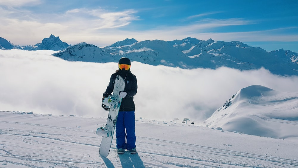 man carrying snowboard standing on snow-covered mountain