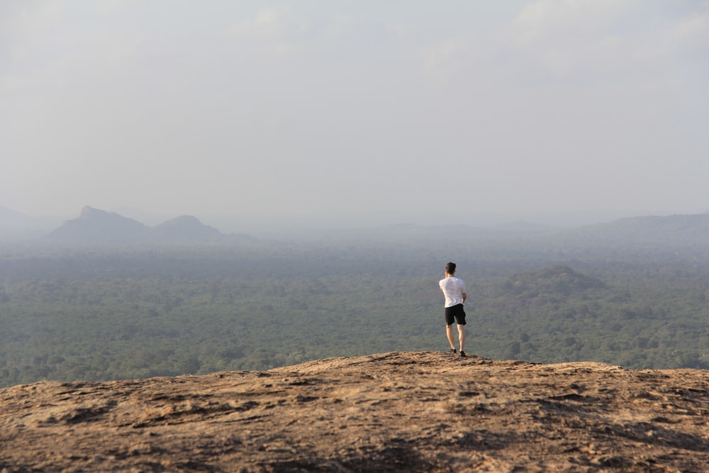 man in white T-shirt standing on mountain during day time