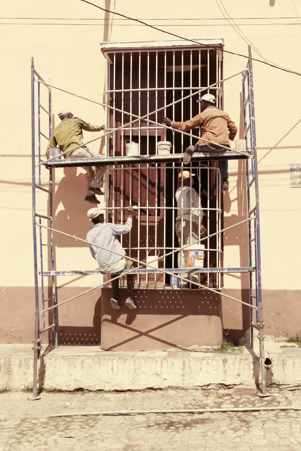 men painting gate