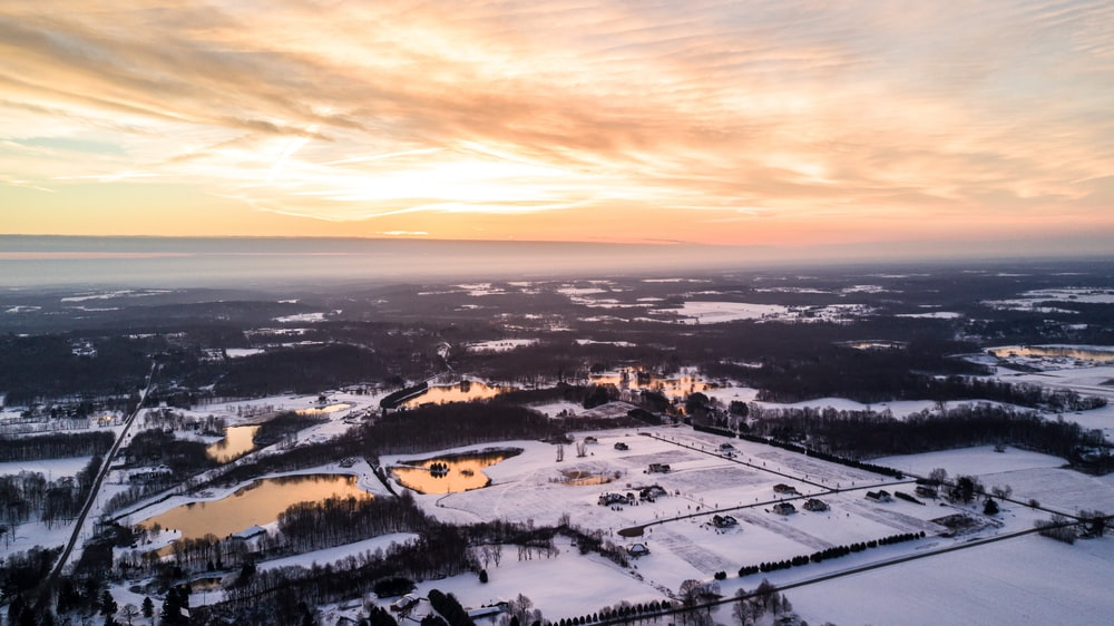 aerial photography of snow covered area under white cloudy skies golden hour photography
