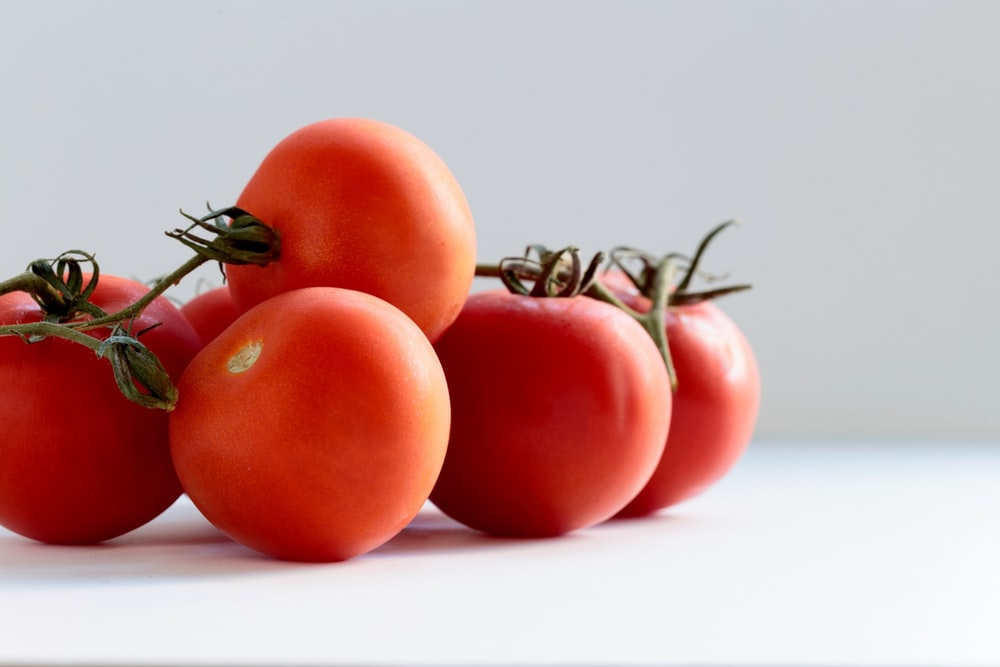 red tomato on white surface