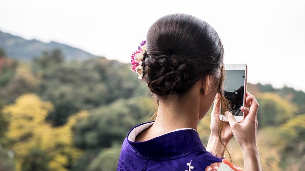 woman taking photo beside trees