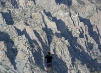 man standing in front gray mountain