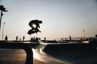 silhouette of man riding skateboard taken at daytime